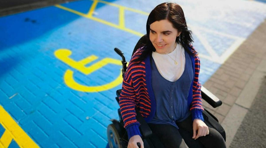 Emma Muldoon pictured seated in her wheelchair in a disabled parking space.