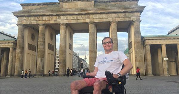PHOTO DESCRIPTION: John in his wheelchair, in front of the Brandenburg Gate in Berlin.