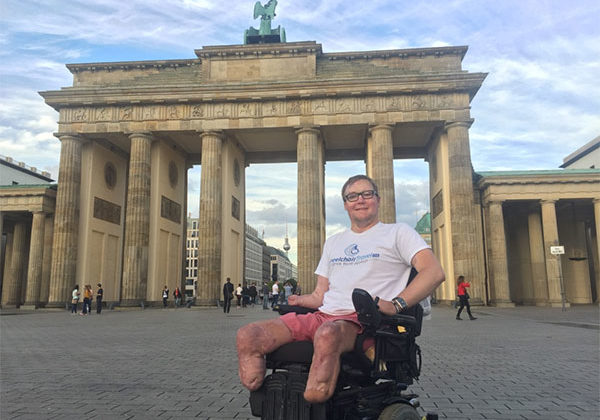 PHOTO DESCRIPTION: John in his wheelchair, in front of the Brandenburg Gate in Berlin.