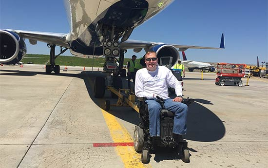 Wheelchair accessible travel guru John Morris in front of a Boeing 757 aircraft.