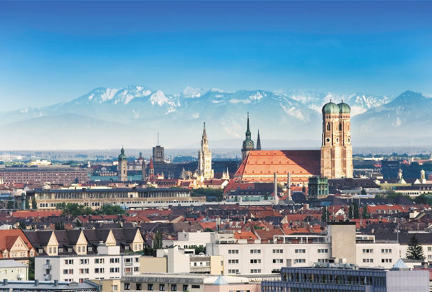PHOTO DESCRIPTION: Munich city skyline from afar on a blue cloudy day, with the Bavarian Alps in the background.
