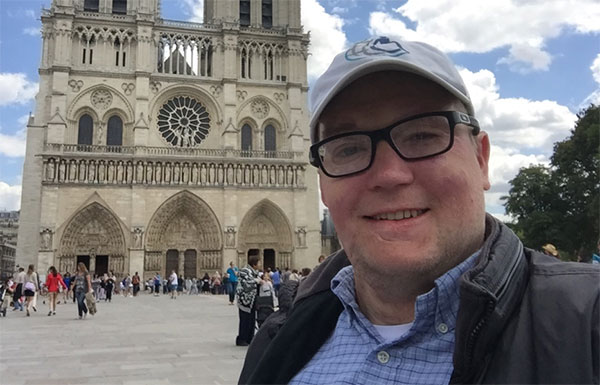 Photo Description: Close-up photo of John Morris in front of the Notre-Dame Cathedral in Paris.
