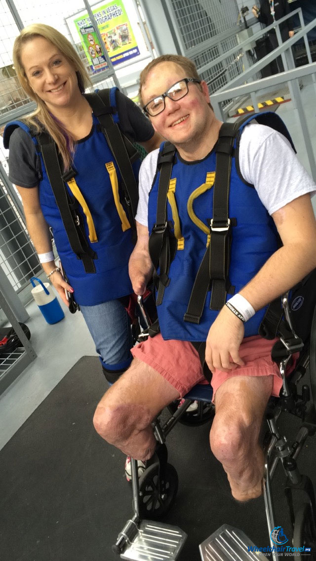 PHOTO DESCRIPTION: John pictured in the SlotZilla wheelchair wearing a safety and attachment harness.