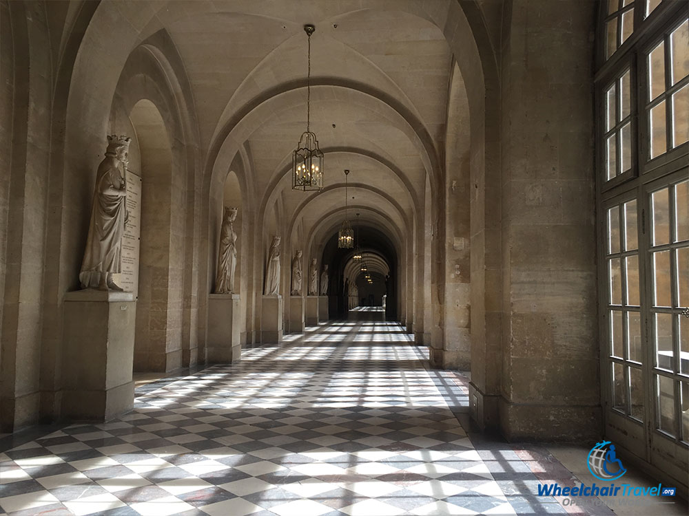 PHOTO DESCRIPTIONS: A long and empty hallway with windows on the right and pedestals topped with statues and busts on the left.