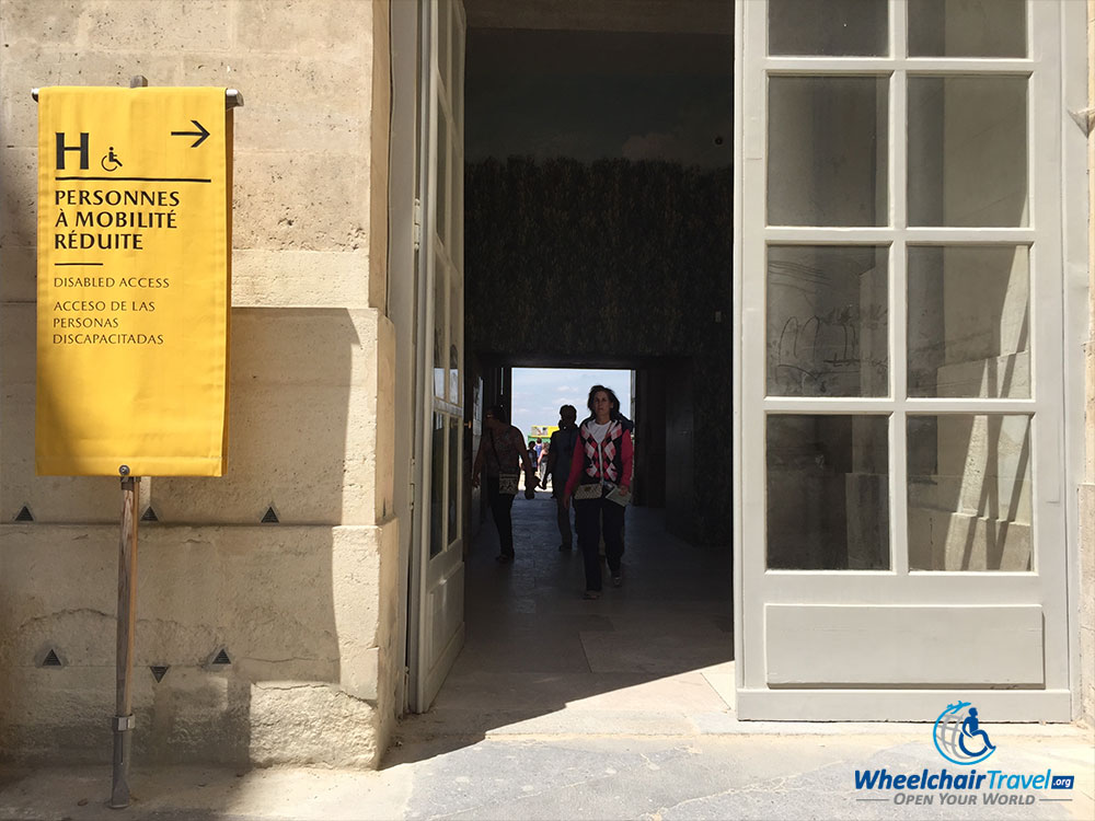 PHOTO DESCRIPTION: Open doorway into the palace, with a yellow banner outside the door that has a bolded letter H, a wheelchair icon and text that reads 'Disabled Access'.