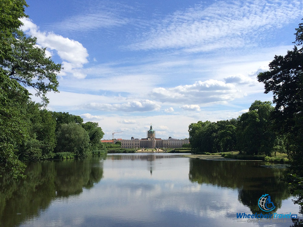 PHOTO DESCRIPTION: The Charlottenburg Palace building, as seen from far across the lake and set against a beautiful blue and white clouded sky.