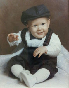PHOTO DESCRIPTION: John Morris as a baby, dressed in overalls and wearing a black cap.