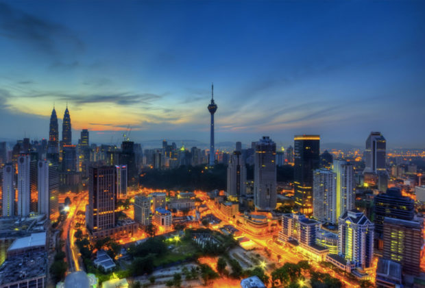 PHOTO DESCRIPTION: Kuala Lumpur, Malaysia skyline at night, with the Petronas Towers and KL Tower clearly visible.