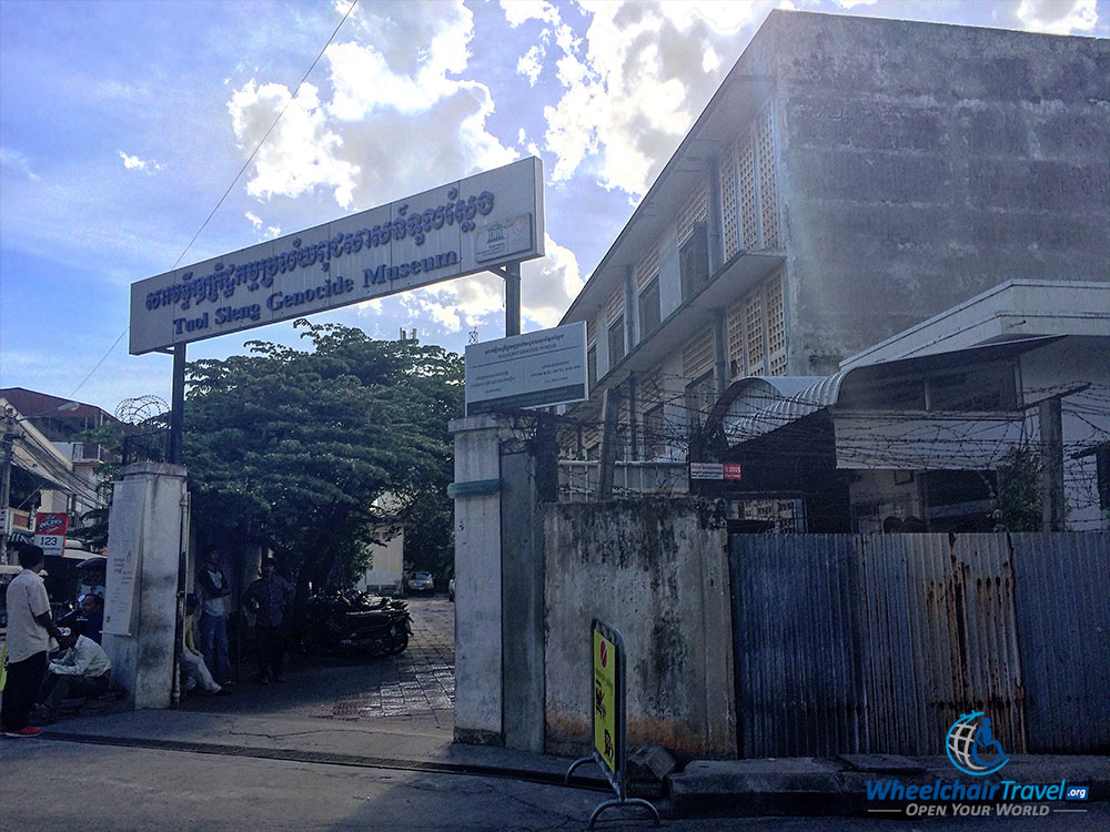 PHOTO DESCRIPTION: Walled property, with a gate on a street corner opened to the museum. Sign above the gate reads TUOL SLENG GENOCIDE MUSEUM.