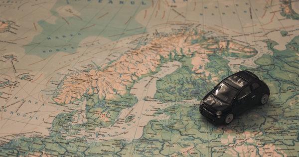 PHOTO: Toy car set atop a large world map.