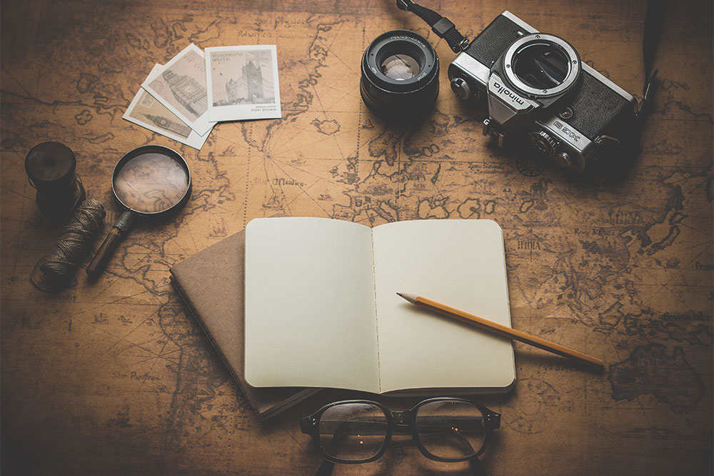 PHOTO: World map with a passport, camera and spectacles laid on top of it.