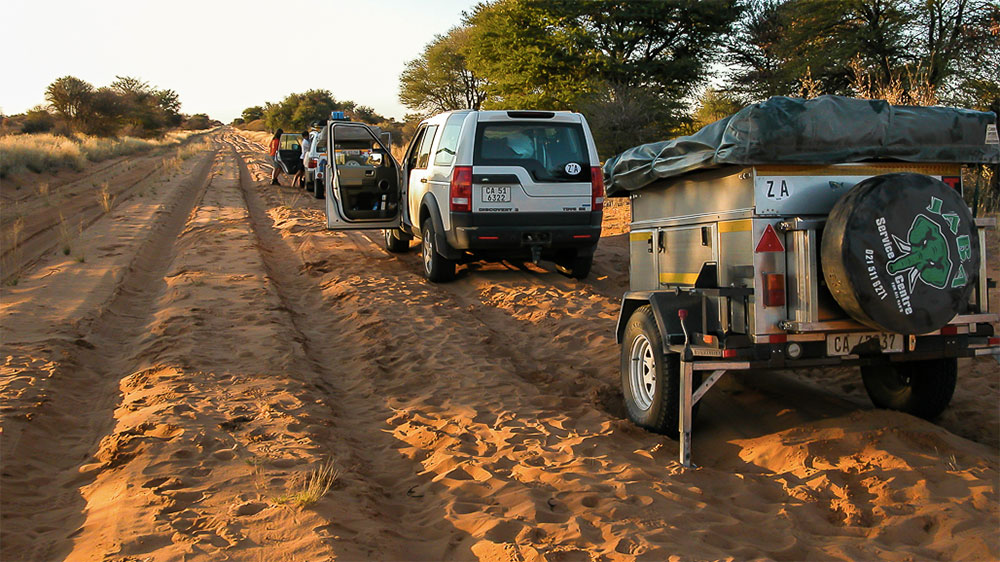 Land Rover with travel trailer parked along a sandy road in Africa