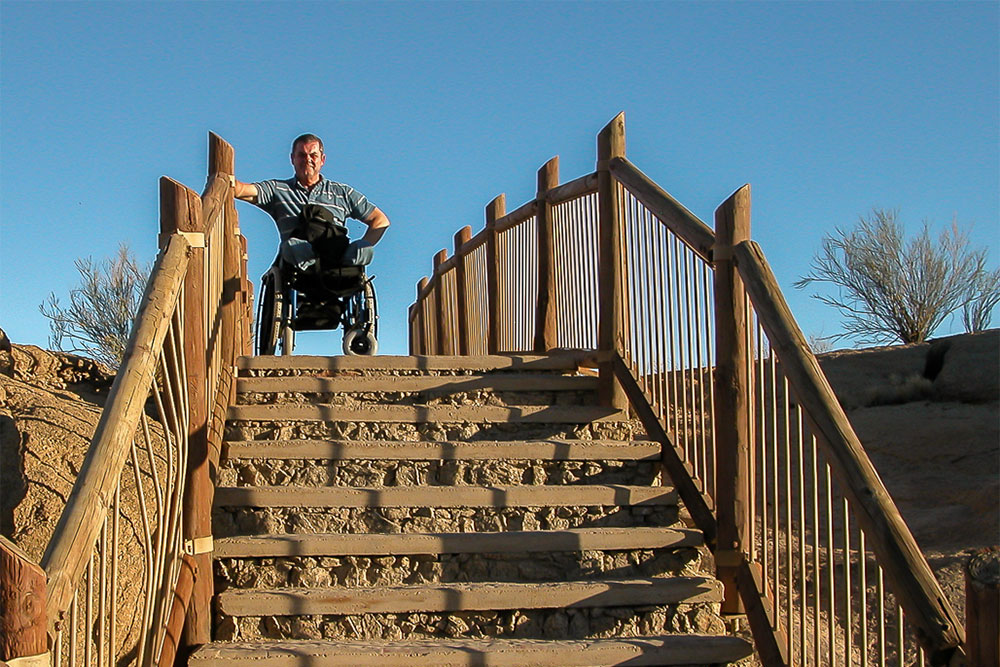 Dave, seated in his wheelchair, at the top of an outdoor set of steps.