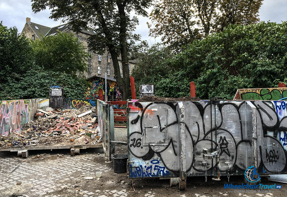 Graffiti on a trash dumpster, with a beautiful home in the background.