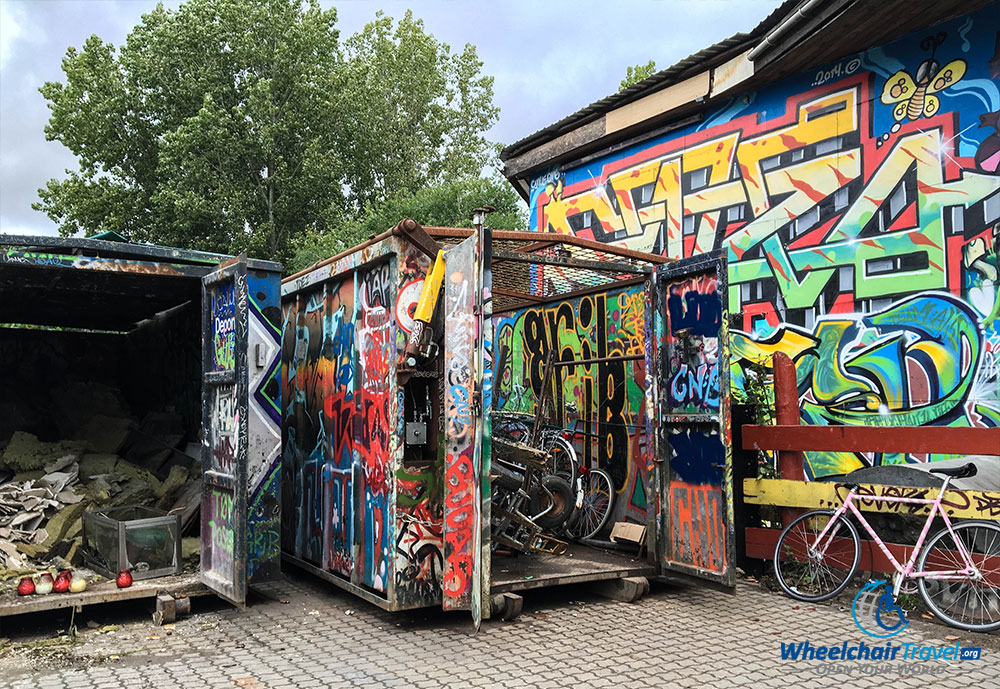 Graffiti painted on the side of a building, spilling over onto a dumpster.