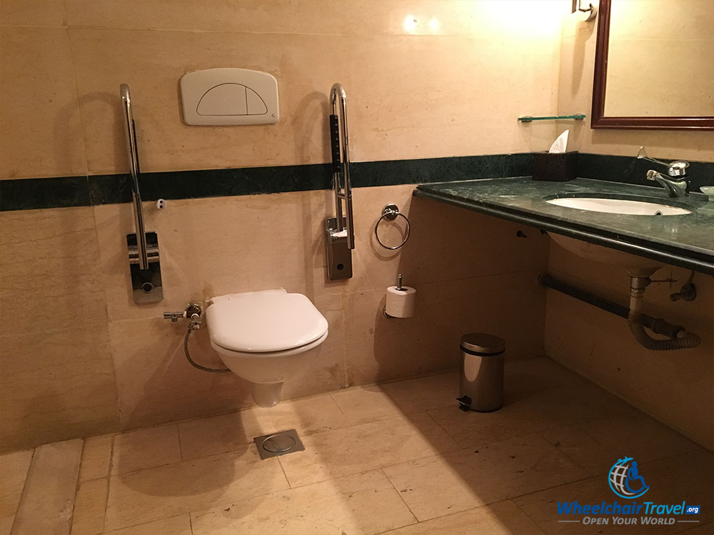 Wheelchair accessible toilet with grab bars, next to a sink.